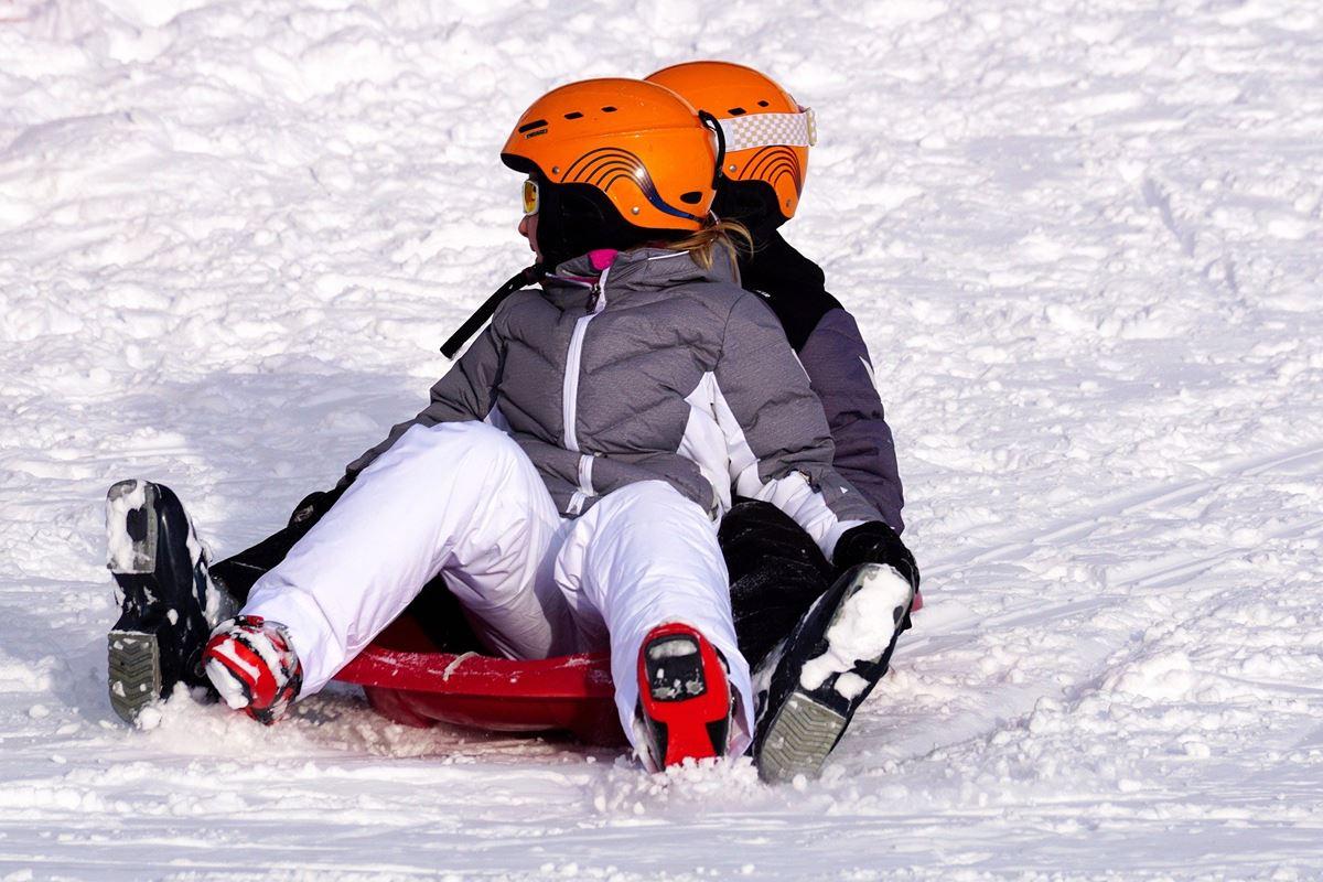 2 Kinder mit Helm beim Bobfahren im Schnee