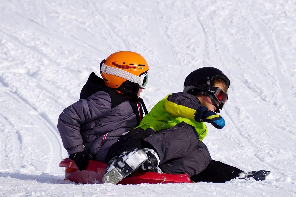 2 Kinder beim Bob fahren im Schnee