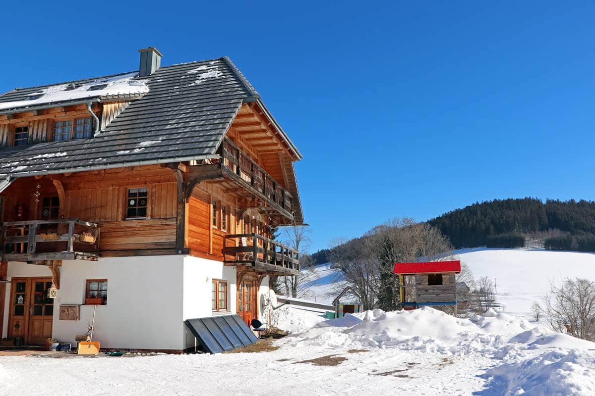 Unter dem Haus im Winter mit Blick auf das Spielhaus mit rotem Dach